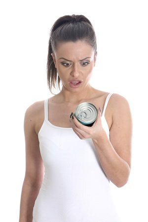 woman-looks-concerned-at-can-of-food