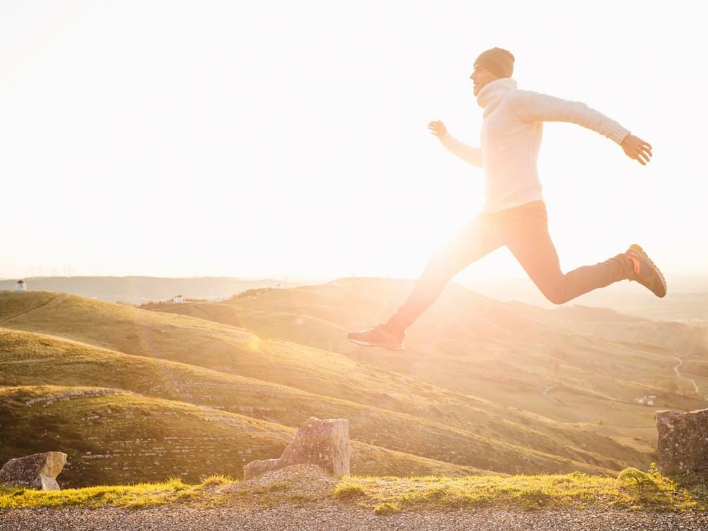 Outdoor runner jumping up midstride